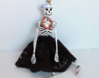 Paper mache Halloween ornament. Skeleton girl in black dress.