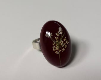 Adjustable ring with cabochon in epoxy resin containing a white field flower.