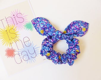 With a bow tie / hair tie / scrunchie elastic fabric with a bow