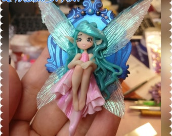 Little Fairy sitting on a shiny cameo frame handmade polymer clay, fimo