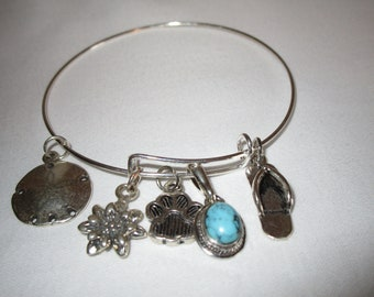 Adjustable sterling silver charm bracelet. Can be stacked with other bangles.