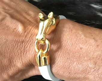 Gold pony clasp on white leather