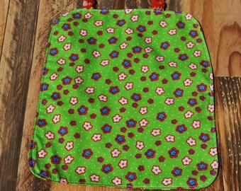 Grande serviette élastiquée réversible coton fleurs sur fond rouge d'un côté et sur fond vert de l'autre
