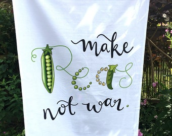 Large cotton tea towel with illustrated and typographic design 'make peas not war'.