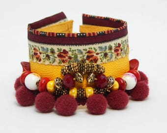 Yellow leather cuff and pom poms