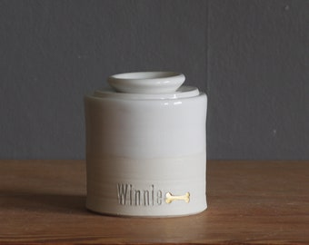 custom urn with lid. shown with gold accent stamp. straight shaped urn with paw stamp. modern simple urn for ashes. white and gold urn.