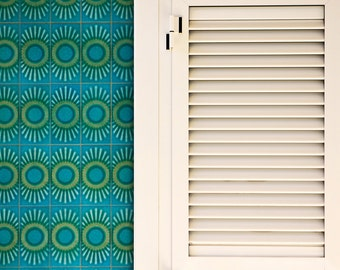 Turquoise and green Spanish tiles on wall with white window shutters in Oliva, Valencia, Spain
