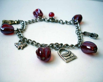 Charm bracelet with red glass beads