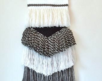 Black and white woven wall hanging on copper