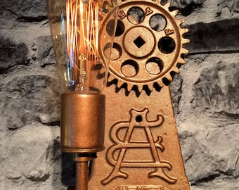 An INDUSTRIAL GEARS  lighted wall art  for Industrial and steampunk art decor.  An Edison bulb lights up this industrial geared lamp.