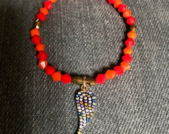 orange and coral red bracelet with wing charm