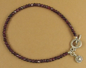 Red garnet bracelet with heart charm dangle. Faceted. Fine and sterling silver.