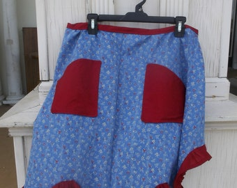 Hand made cotton half apron blue background with red and white flowers with a red ruffle and red pockets that just make this apron.