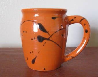 Orange splatter print mug on red clay