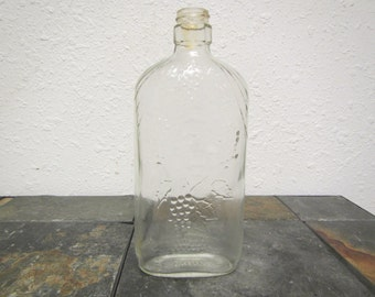 vintage Clear Glass  GRAPE WINE BOTTLE with raised Grape clusters  and vines 1876 on bottom ; 1 pint