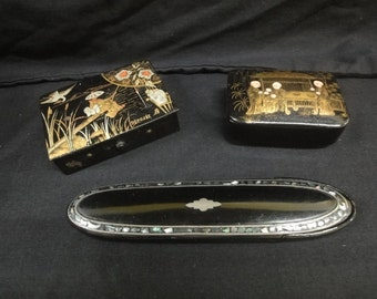 Two small chinoiserie lacquered papier mache boxes together with a papier mache spectacle case