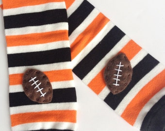 Snack Size Leg Candy Football Baby Leg Warmers: black, orange and white stripes with footballs