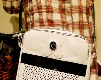 White and black leather messenger bag.