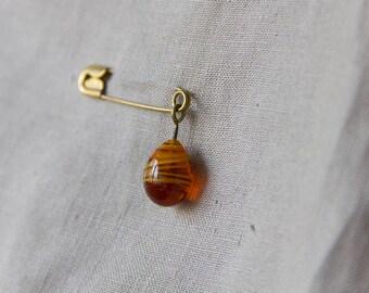 big dark honey swirl drop on safety pin, brooch vintage brass and amber glass