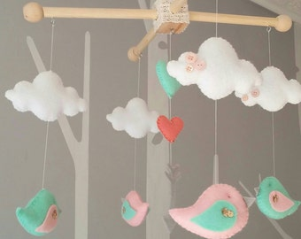 Soft pink & mint bird mobile with arrows and clouds.