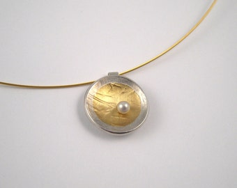 Elegant round gold silver pendant with rough surface and a pearl.