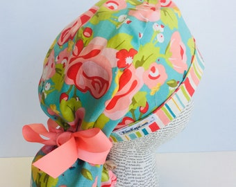 Ponytail Scrub Cap scrub hat with a light blue material with flowers in pink and green with a coordinating band and matching ribbon 2t