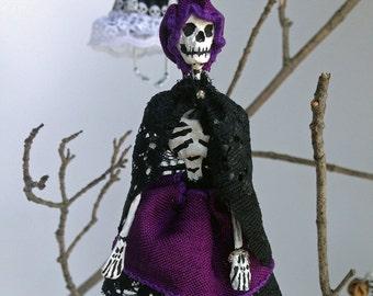 Paper mache Halloween ornament. Skeleton girl in purple and black dress.