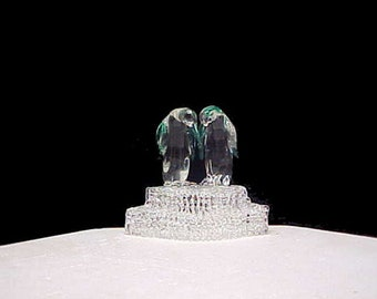 Penguin wedding cake topper with two penguins on a base.