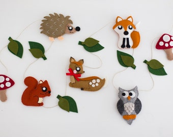 Woodland creatures nursery garland featuring fox, owl, squirrel, deer, hedgehog and toadstools.