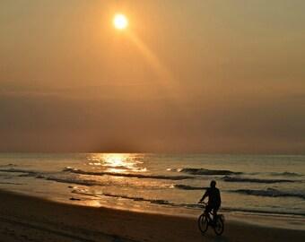 Man enjoying an early morning ride on the beach.