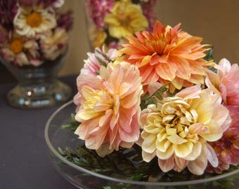 Centerpiece of sunny dahlias on a glass cake platter with lid.