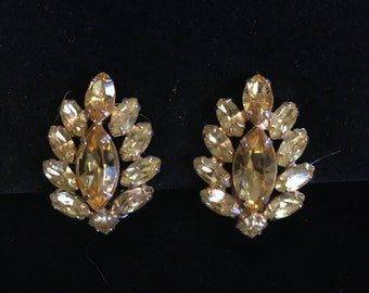 Vintage gold tone costume jewelry clip earrings with yellow stones .