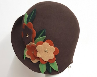 Chocolate brown cloche hat with brown tone flowers and green leaves flapper style with upturn front brim wool felt
