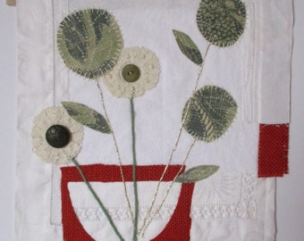 Textile art, appliqued and embroidered flower still life on vintage and recycled fabrics, with vintage buttons. Unframed on white mountboard