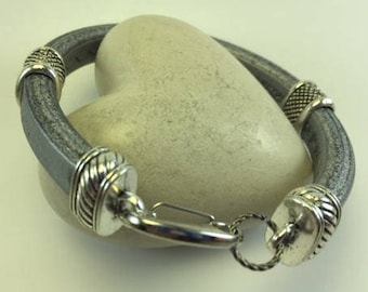 Sturdy silver colored bracelet with silver sliders and closure on licorice leather
