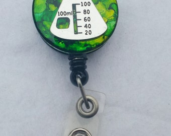 Science beaker name badge holder with a green background