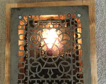 A pair of Victorian heating vents turned into accent lighting for your wall.