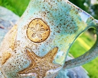Handmade aqua starfish and sand dollar coffee mug. Wheel thrown pottery!