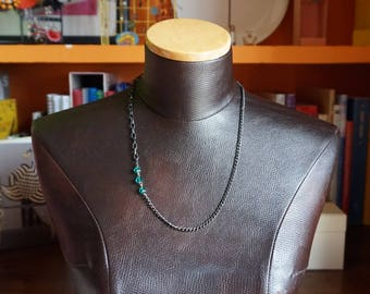 Asymmetrical chain pendant with green detail.