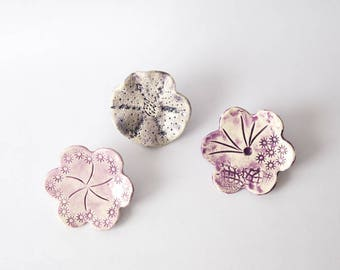 3 flowers in shades of purple with imprints of motis ceramic