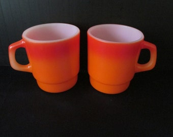 A Pair of Fire King Orange Stackable Coffee Mugs. / Cups