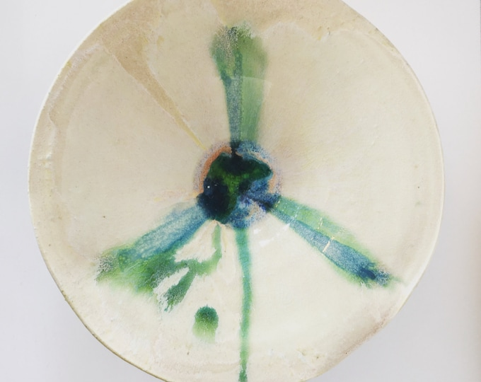 Off white hand thrown ceramic bowl with green, blue, and turquoise.