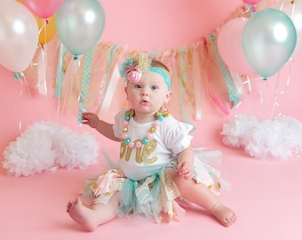 baby girls first birthday, shabby chic skirt, romper onesie with gold ONE, flower hairclip, gold shoes, chunky necklace in aqua, pink, gold