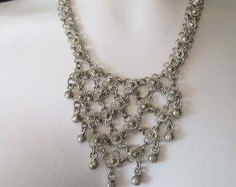Woven silver metal flowers cascade down this beautiful necklace