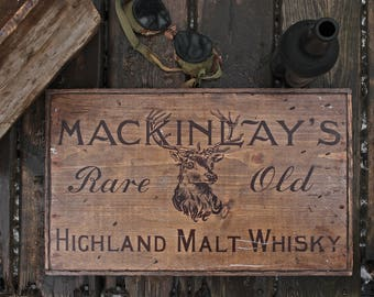 Vintage wooden sign ' 1907 Expedition MacKinlay's Whisky' reproduction concept.