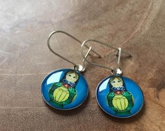 Dangeling Matryoshka earrings: light blue, yellow and green.