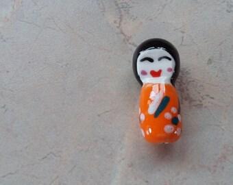 Kokeshi doll ceramic beads, orange.