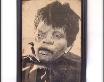 Aged reproduction print of a freaky Quasimodo looking child in frame.
