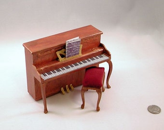 Antique  mahogany spinet piano with sheet music, raspberry upholstery bench. 1 to 12 scale.  Hand made in USA.