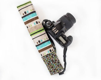 DSLR camera strap cover with lens cap pocket.  brown, blue and green stripe with squares
